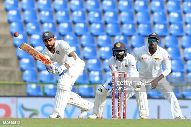 Indian cricket captain Virat Kohli is watched by Sri Lankan wicketkeeper Niroshan Dickwella and Angelo Mathews as he plays a shot during the first...