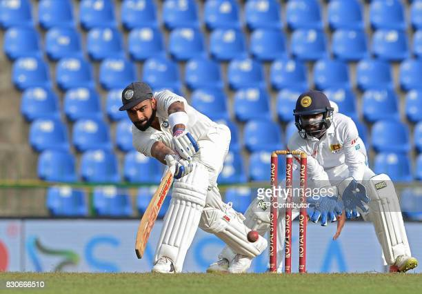 Indian cricket captain Virat Kohli is watched by Sri Lankan wicketkeeper Niroshan Dickwella as he plays a shot during the first day of the third and...