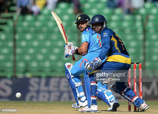 Indian cricket captain Virat Kohli plays a shot as Sri Lankan wicketkeeper Kumar Sangakkara looks on during the fourth match of the Asia Cup oneday...