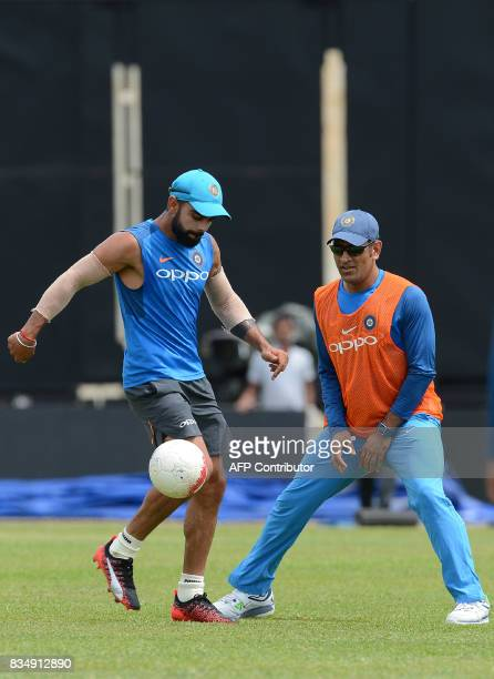 Indian cricket captain Virat Kohli plays football with teammate Mahendra Singh Dhoni during a practice session at the Rangiri Dambulla International...