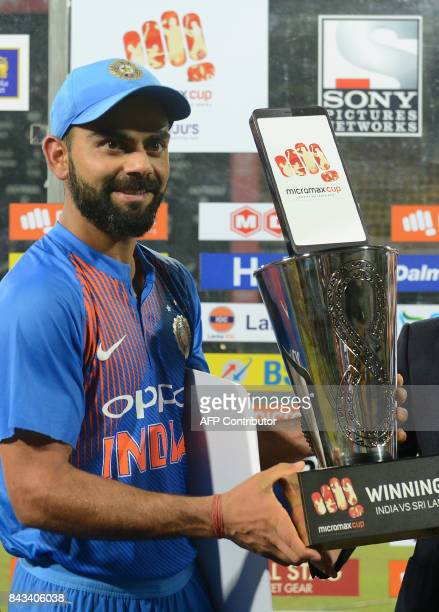 Indian cricket captain Virat Kohli poses with the trophy after winning the Twenty20 international cricket match between Sri Lanka and India at R...