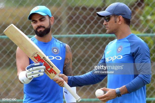 Indian cricket captain Virat Kohli speaks with his teammate Mahendra Singh Dhoni during a practice session at the Rangiri Dambulla International...