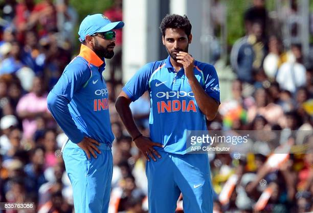 Indian cricket captain Virat Kohli speaks with teammate Bhuvneshwar Kumar during the first One Day International cricket match between Sri Lanka and...