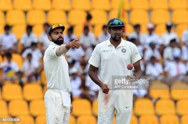 Indian cricket captain Virat Kohli speaks with teammate Ravichandran Ashwin during the third day of the third and final Test match between Sri Lanka...