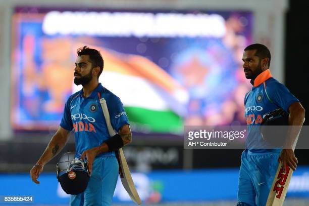 Indian cricket captain Virat Kohli teammate Shikhar Dhawan leave the grounds after victory in the first One Day International cricket match between...