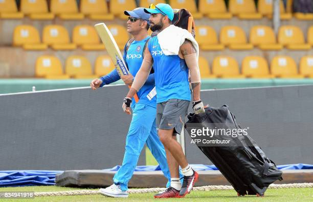 Indian cricket captain Virat Kohli walks with his teammate Mahendra Singh Dhoni upon their arrival during a practice session at the Rangiri Dambulla...