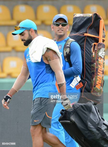 Indian cricket captain Virat Kohli walks with his teammate Mahendra Singh Dhoni upon their arrival for a practice session at the Rangiri Dambulla...