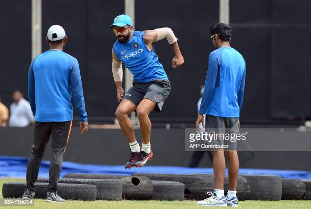 Indian cricket captain Virat Kohli warms up as teammates look on during a practice session at the Rangiri Dambulla International Cricket Stadium in...