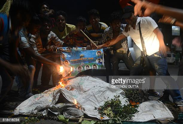 Indian cricket fans burn portraits of players as they stage a funeral of the Indian cricket team in the streets of Siliguri on March 31 after India's...
