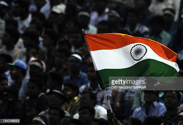 Indian cricket fans celebrate as they wave their national flag during the first One Day International match between Indian and West Indies at the...