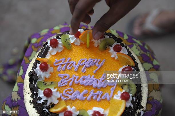 Indian cricket fans place a candle on a cake to celebrate the birthday of cricketer Sachin Tendulkar in a media organised event in Hyderabad on April...