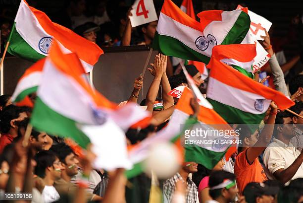Indian cricket fans wave national flags during the second day of the second Test between India and Australia at MChinnaswamy Stadium in Bangalore on...