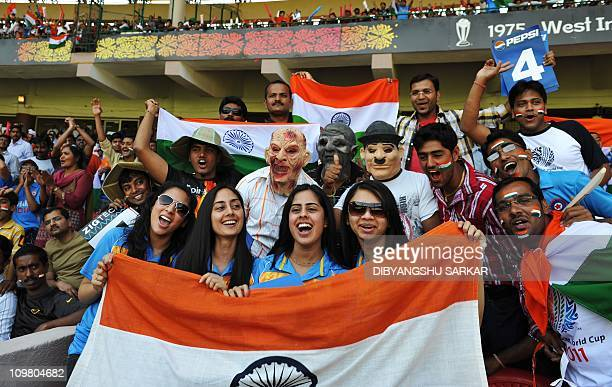 Indian cricket fans wearing masks wave national flags as they cheer for their team prior to the Cricket World Cup 2011 match between India and...