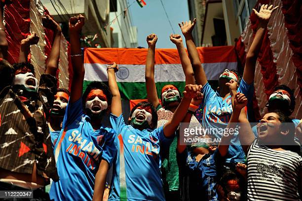 Indian cricket fans with their faces painted in the colours of the national flag cheer after offering special prayers in Hyderabad on March 30 2011...