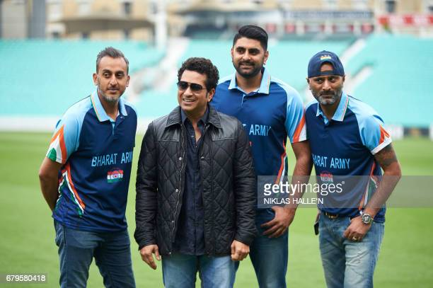 Indian cricket legend Sachin Teldulkar poses for a photograph with members of the Bharat Army during a photocall at the Oval cricket ground in south...