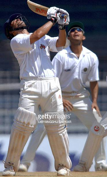 Indian cricket player Sachin Tendulkar looks at the ball he just hit as Sourav Ganguly looks on during the third day of the fiveday Irani Trophy in...