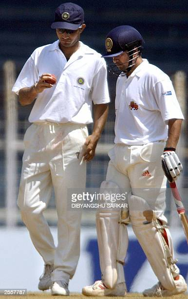 Indian cricket player Sachin Tendulkar walks by Sourav Ganguly who takes a close look at the ball during the third day of the fiveday Irani Trophy in...