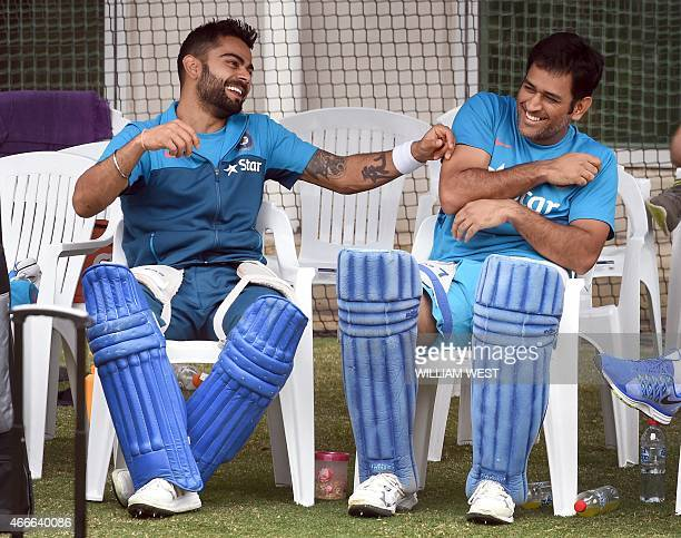 Indian cricket players Virat Kohli and captain Mahendra Singh Dhoni share a lighter moment during a training session ahead of their 2015 Cricket...