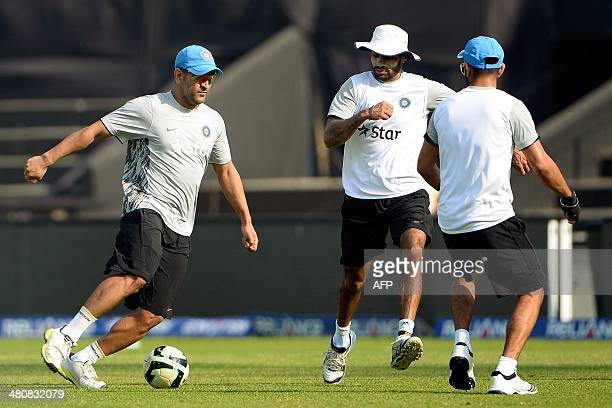 Indian cricket team captain Mahendra Singh Dhoni plays football with teammates Shikhar Dhawan and Virat Kohli during a training session at The...