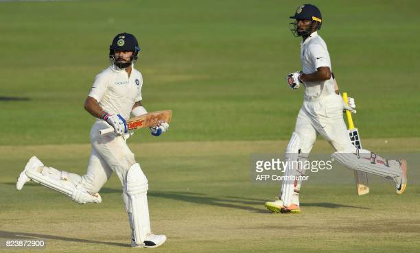 Indian cricket team captain Virat Kohli and Abhinav Mukund run between the wickets during the third day of the first Test match between Sri Lanka and...