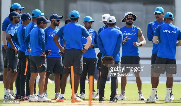 Indian cricket team captain Virat Kohli and newlyappointed coach Ravi Shastri chat with team members during a practice session at Galle International...