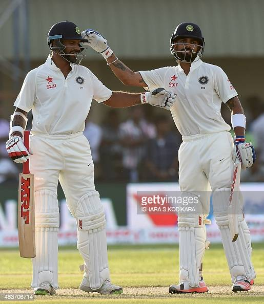 Indian cricket team captain Virat Kohli and Shikhar Dhawan gesture during the first day of the opening Test match between Sri Lanka and India at the...