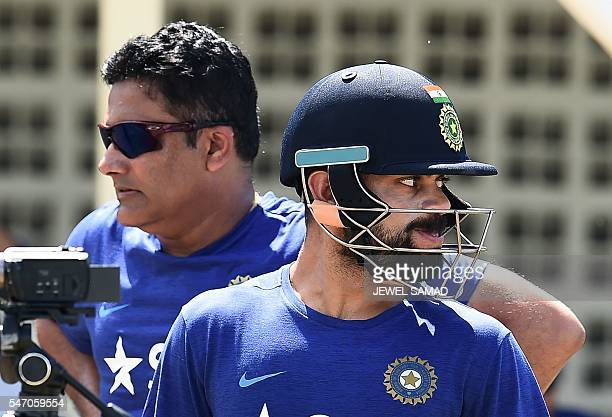 Indian cricket team captain Virat Kohli and team head coach Anil Kumble watch their teammates during a practice session at the Warner Park stadium in...