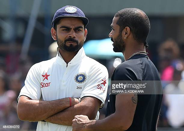 Indian cricket team captain Virat Kohli and teammate Shikhar Dhawan speak after defeat on the fourth day of the opening Test match between Sri Lanka...