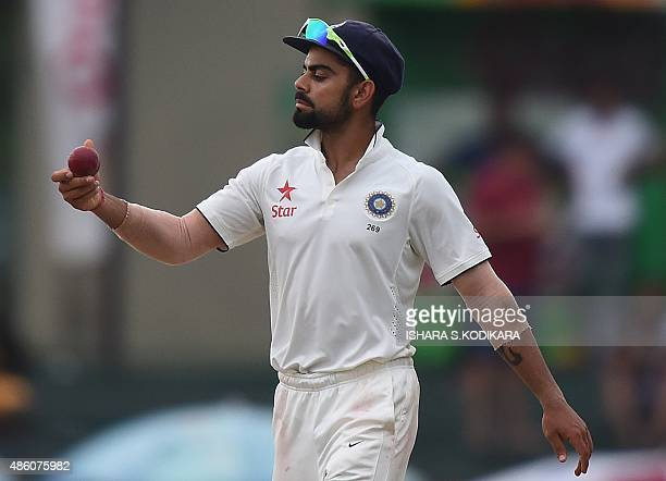Indian cricket team captain Virat Kohli examines the ball during the fourth day of their third and final Test cricket match between Sri Lanka and...
