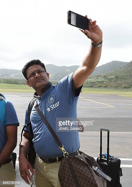 Indian cricket team head coach Anil Kumble takes a selfie upon arrival at the airport in Basseterre Saint Kitts on July 6 2016 Indian cricket team...