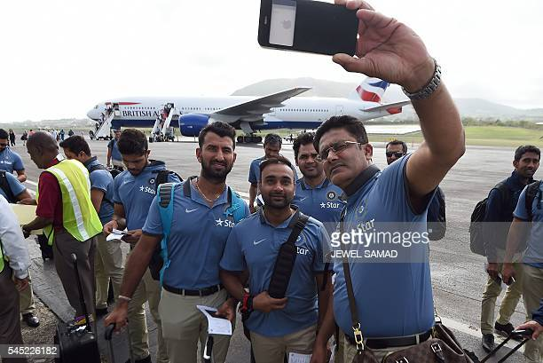 Indian cricket team head coach Anil Kumble takes a selfie with his team upon arrival at the airport in Basseterre Saint Kitts on July 6 2016 Indian...