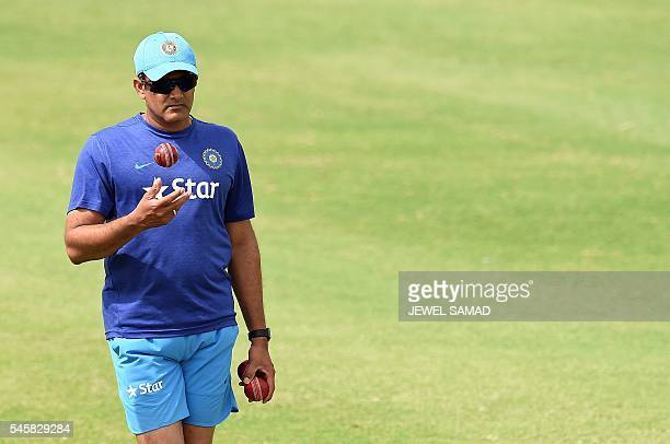 Indian cricket team head coach Anil Kumble tosses a ball as he watches his team warming up before the start of the second day of a twoday tour match...