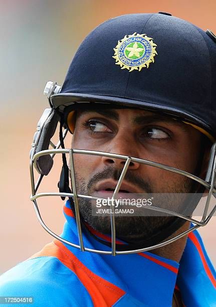 Indian cricket team's acting captain Virat Kohli leaves the field after being dismissed during the third match of the TriNation series between India...
