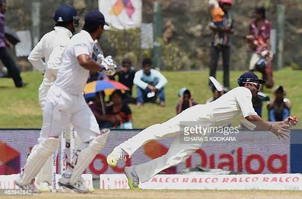 Indian cricketer Ajinkya Rahane dives to take a catch to dismiss Sri Lankan batsman Kumar Sangakkara during the third day of the opening Test match...