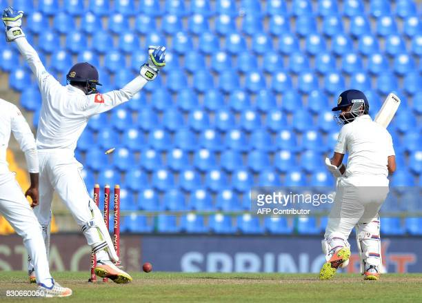 Indian cricketer Ajinkya Rahane gets dismissed by Sri Lankan spinner Malinda Pushpakumara as wicketkeeper Niroshan Dickwella looks on during the...