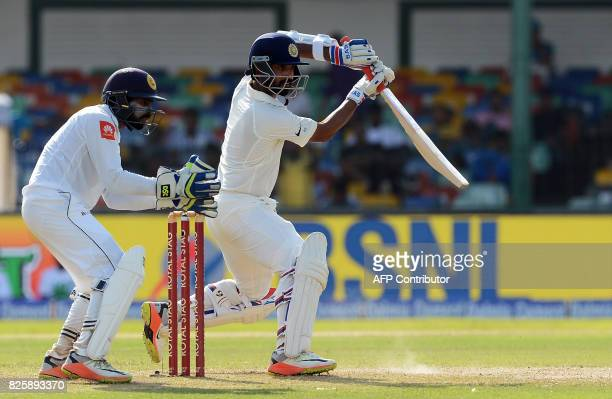 Indian cricketer Ajinkya Rahane is watched by Sri Lankan wicketkeeper Niroshan Dickwella as he plays a shot during the first day of the second Test...