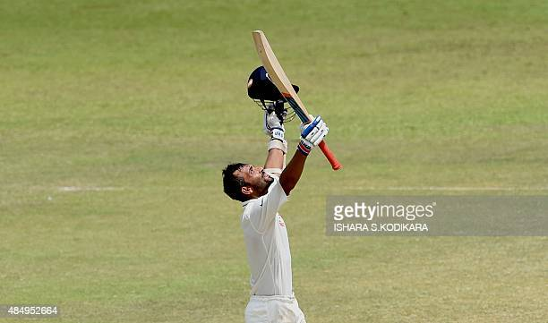 Indian cricketer Ajinkya Rahane raises his bat and helmet in celebration after scoring a century during the fourth day of the second Test match...