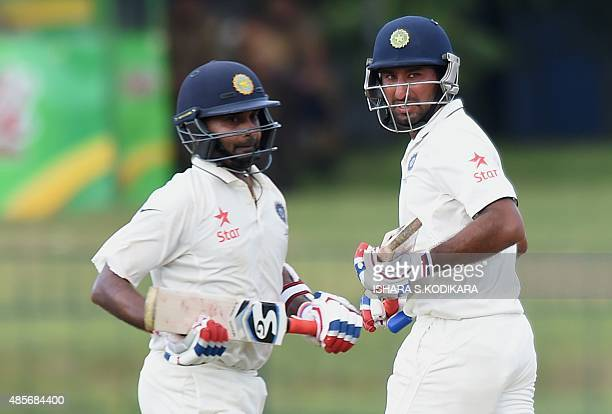 Indian cricketer Amit Mishra and Cheteshwar Pujara run between the wickets during the second day of the third and final Test cricket match between...