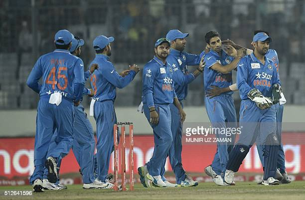 Indian cricketer Ashish Nehra celebrate with teammates after the dismissal of the Pakistan cricketer Mohammad Hafeez during the match between India...