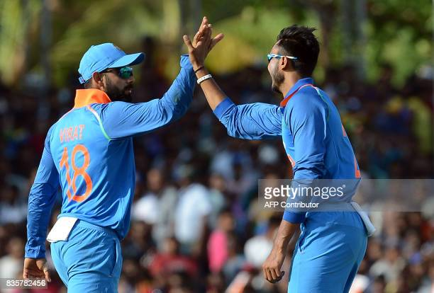 Indian cricketer Axar Patel celebrates with his captain Virat Kohli after he dismissed Sri Lankan cricketer Kusal Mendis during the first One Day...