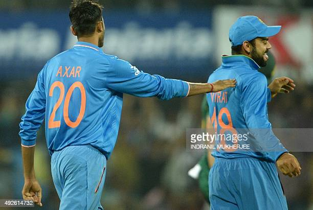 Indian cricketer Axar Patel congratulates teammate Virat Kohli for taking a catch off his bowling to claim the wicket of South Africa's Faf du...