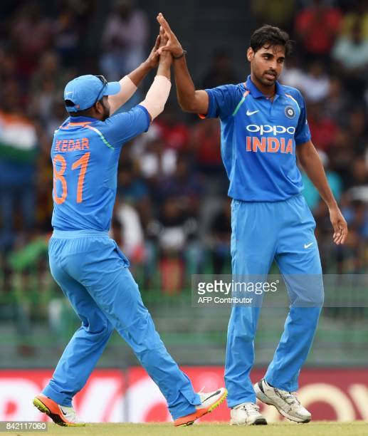Indian cricketer Bhuvneshwar Kumar celebrates with his teammate after dismissing Sri Lankan cricketer Niroshan Dickwella during the final one day...