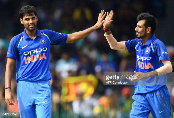 Indian cricketer Bhuvneshwar Kumar celebrates with teammate Yuzvendra Chahal after he dismissed Sri Lankan cricketer Dilshan Munaweera during the...