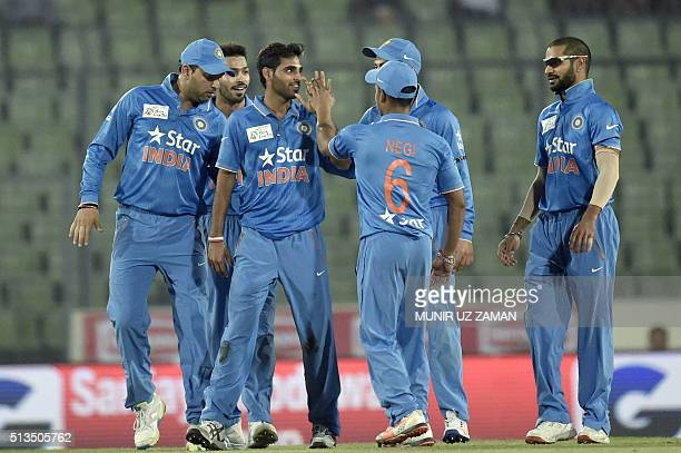 Indian cricketer Bhuvneshwar Kumar celebrates with teammates after the dismissal of unseen United Arab Emirates batsman Swapnil Patil during the Asia...