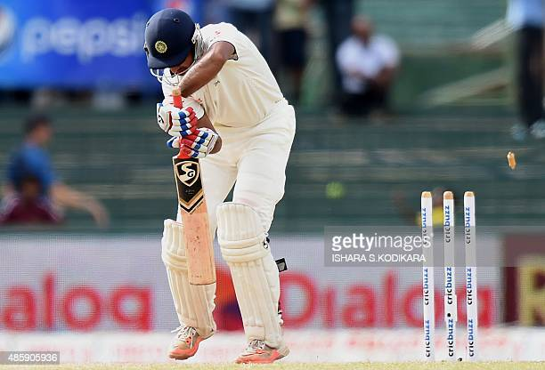 Indian cricketer Cheteshwar Pujara is dismissed by Sri Lankan cricketer Dhammika Prasad during the third day of their third and final Test cricket...
