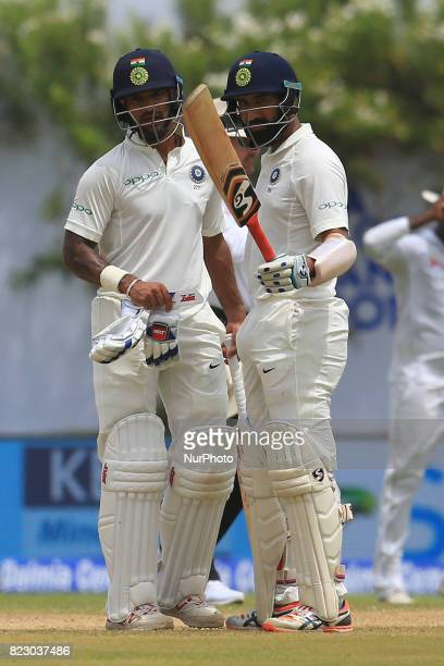 Indian cricketer Cheteshwar Pujara raises his bat after scoring 50 runs as his partner Shikhar Dhawan looks on during the 1st Day's in the 1st Test...