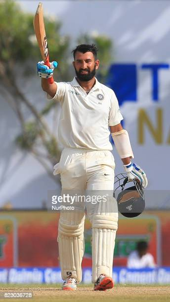 Indian cricketer Cheteshwar Pujara raises his bat after scoring a century during the 1st Day's play in the 1st Test match between Sri Lanka and India...