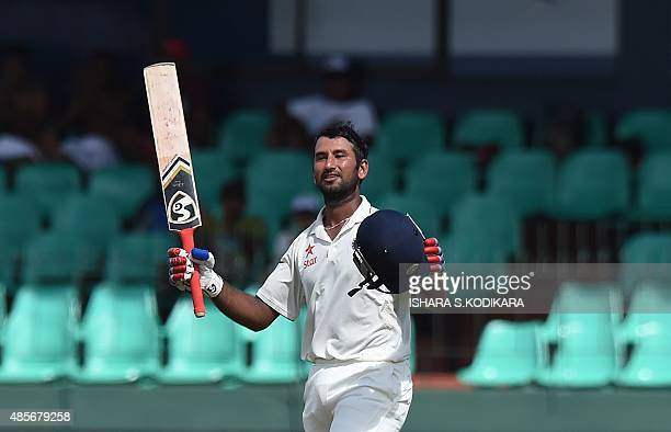 Indian cricketer Cheteshwar Pujara raises his bat and helmet in celebration after scoring a century during the second day of their third and final...