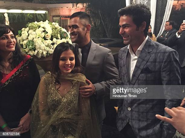 Indian cricketer MS Dhoni with his wife Sakshi Dhoni and cricketer Mohammad Kaif during the wedding reception of Indian Cricketer Yuvraj Singh and...