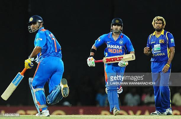 Indian cricketer Gautam Gambhir and captain Mahendra Singh Dhoni run between wickets as Sri Lankan cricketer Lasith Malinga looks on during the third...